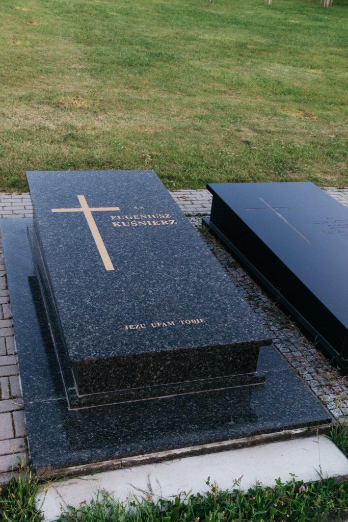 Nagrobek granitowy sarkofag, z krzyżem złotym i napisami na nakrywie a w tle zielona trawa
